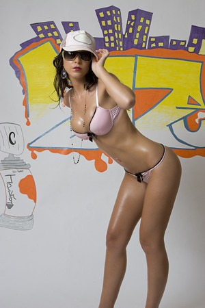Beautiful brunette lingerie model with sunglasses and baseball cap in front of graffitied wall bending forward photo