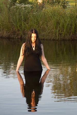 twenty something women with long black hair, wearing a black evening dress, waist deep in a lake at sunset photo