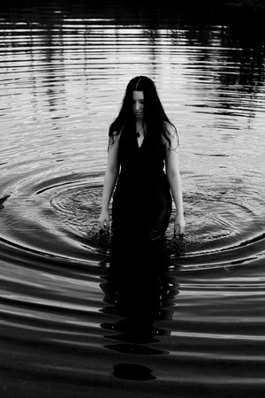 river: twenty something women with long black hair, wearing a black evening dress, walking out of the water