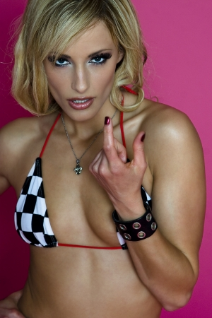 young women wearing a racing strip sting bikini against a pink background showing with her finger how small something is photo