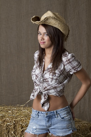 brunette cowgirl standing in front of bales of straw photo