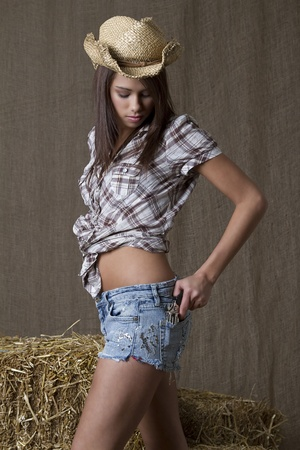 Young brunette cowgirl putting a small gun in her back pocket in front of bales of straw photo