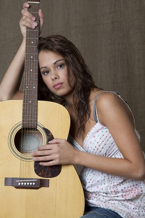 sassy: young brunette girl leaning on accoustic guitar