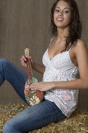 young brunette woman sitting on bales of hay and playing a toy ukulele photo