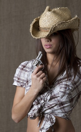 Young brunette cowgirl blowing on a small gun  photo