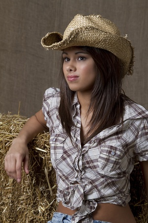 portrait of a young brunette cowgirl against a brown background Stock Photo - 8358455