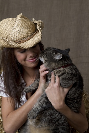 brunette cowgirl sitting on a bales of straw with her pet cat photo