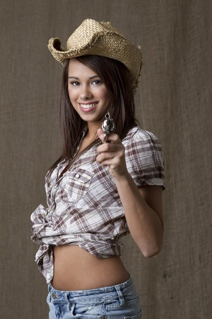 Young brunette cowgirl with a small gun pointed at the camera Stock Photo - 8537452