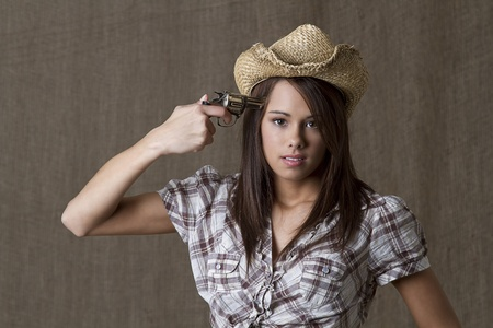Young brunette cowgirl with a small gun pointed to her head photo
