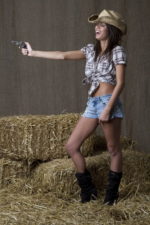 Young brunette cowgirl with small gun laughing her heart out photo
