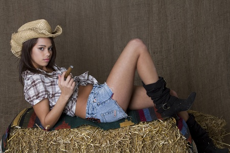 Young brunette cowgirl smoking a cigar relaxing on top bales of straw Stock Photo - 8537480