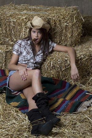 Young brunette cowgirl relaxing on a blanket laid on some straw and smoking a cigar Stock Photo - 8537518