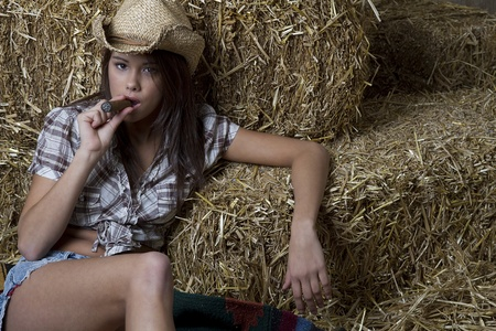 Young brunette cowgirl relaxing and smoking a cigar with her back to bales of straw photo