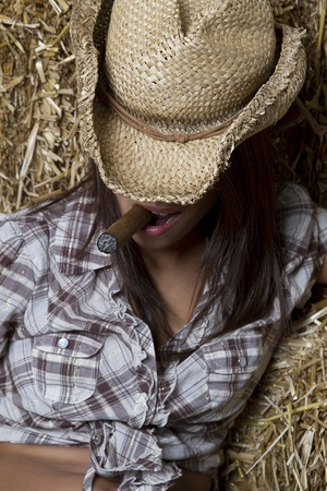 Young brunette cowgirl smoking a cigar relaxing against bales of straw with her hat down photo