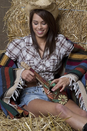young brunette cowgirl sitting in the straw, wrap in a blanket, playing a ukulele photo
