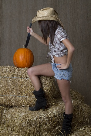 stabbing: young brunette cowgirl stabbing a pumpkin set of some bales of straw