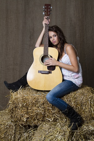 young brunette girl leaning on accoustic guitar photo