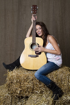 young brunette girl leaning on accoustic guitar