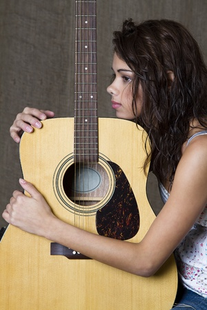 girl playing guitar: young brunette girl hugging an accoustic guitar Stock Photo