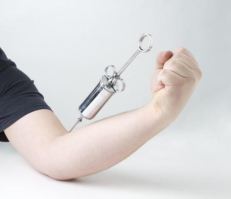 male arm: jeringa metal en rama masculina sobre fondo blanco