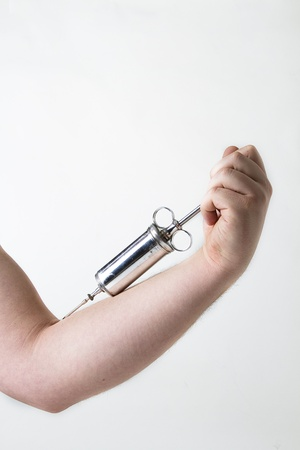 metal syringe in male arm against white background Stock Photo - 8800616