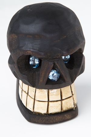 two oval cut blue topaz set as eye and one radiant cut blue topaz set in the nose of a wooden skull photo