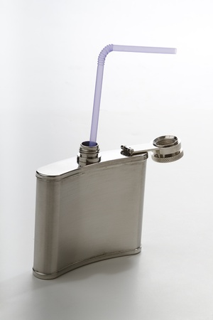 tipple: metal flask with purple straw against a white background Stock Photo