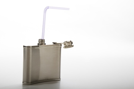 metal flask with purple straw against a white background Stock Photo