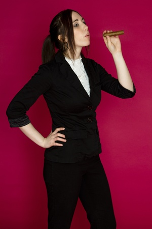 cigar smoking woman: Young woman in a business suit blowing smoke from a cigar against a pink background Stock Photo