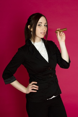 Young woman in a business suit smoking a cigar against a pink background photo