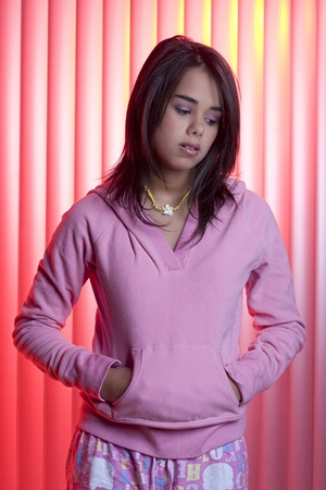 Teenage girl with sad expression wearing a pink pajama Stock fotó