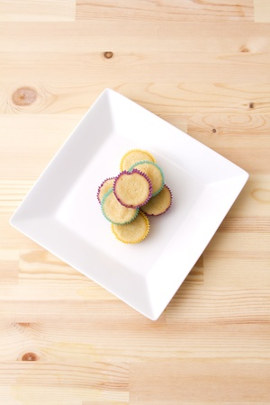 undecorated: Plate of small undecorated cupcake in multicolored paper cup Stock Photo