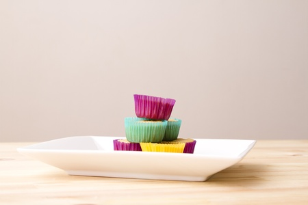 Plate of small undecorated cupcake in multicolored paper cup photo
