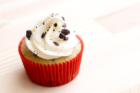 Cupcake in rode papier cup op een houten tafel met vanille slagroom en cookie kruimels