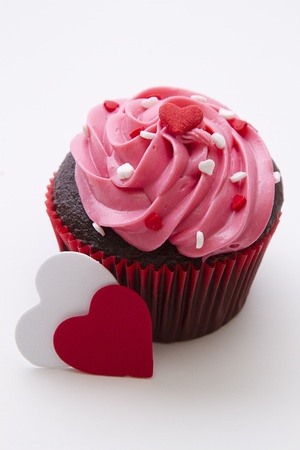 Chocolate cupcake decorated with pink frosting and candy hearts