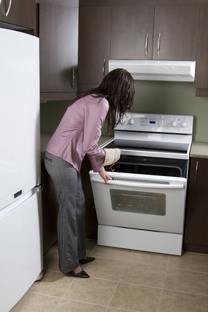 Woman standing in front of open oven with one oven mit Archivio Fotografico