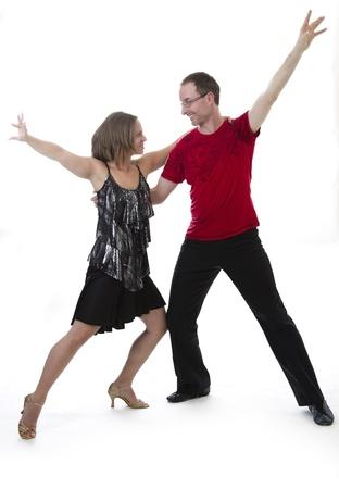 bailar salsa: El hombre y la mujer bailando salsa mir�ndose a los ojos de otro tipo contra un fondo blanco Foto de archivo