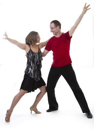 Man and woman dancing salsa looking into each other eyes against a white background