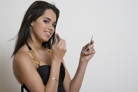 Young woman applying lipstick against a white background