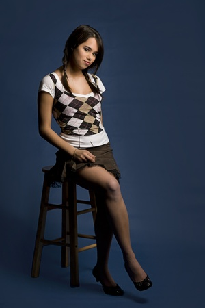 Teen girl with student look sitting on a stool