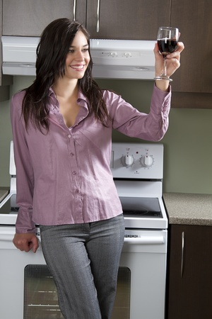range of motion: young woman standing in front of range appliance, holding a glass a red wine in cheer motion