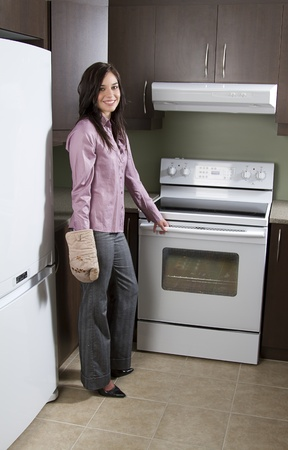 Woman standing in front of an oven with one oven mit, about to open the door. photo