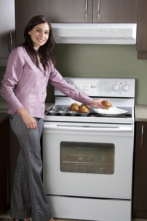 Young woman standing in front of an oven, placing muffins on a plate
