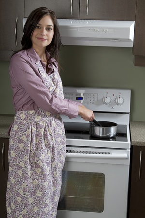 Young woman with apron, stirring a pot on the stove photo