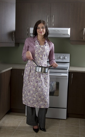 Young woman with apron, stirring a pot in front of the stove