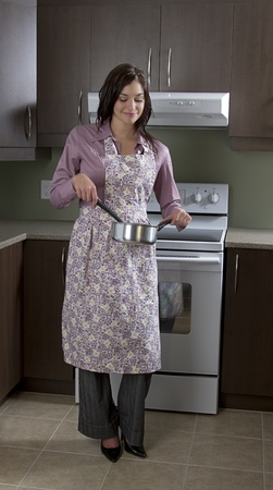 Young woman with apron, stirring a pot in front of the stove photo