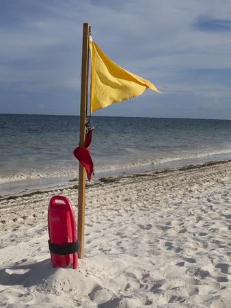 flotation: Lifeguard flotation device and warning flag on the beach