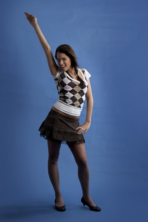 Young girl wearing a mini-skirt pointing up with her arm photo