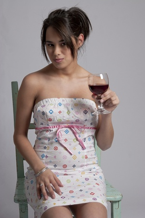 young woman holding a glass of red wine photo