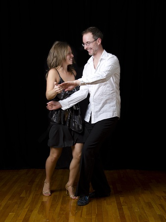 couple dancing salsa in the middle of a pose photo